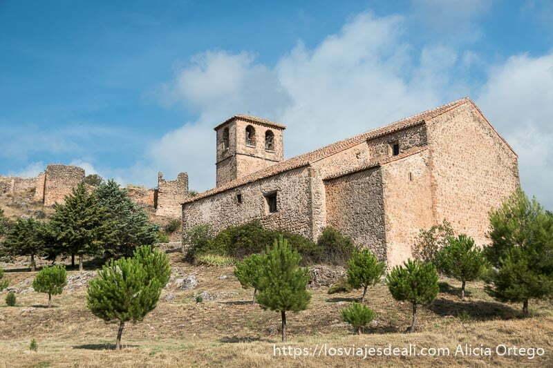 iglesia de Riópar viejo toda de piedra con su campanario y la muralla árabe detrás bajo cielo azul con nubes y pequeños pinos en primer plano en la escapada a albacete