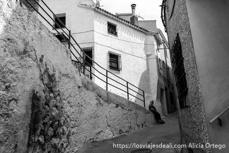 calle de pueblo en cuesta con otra calle que baja en rampa y una casa blanca al fondo con mujer sentada