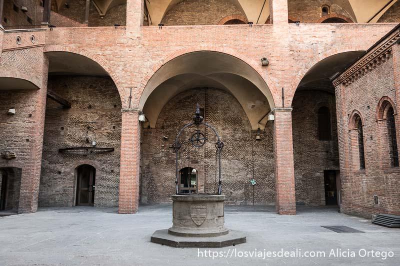 patio de un palacio con grandes arcos todo de ladrillo y un pozo en el centro imprescindibles de bolonia