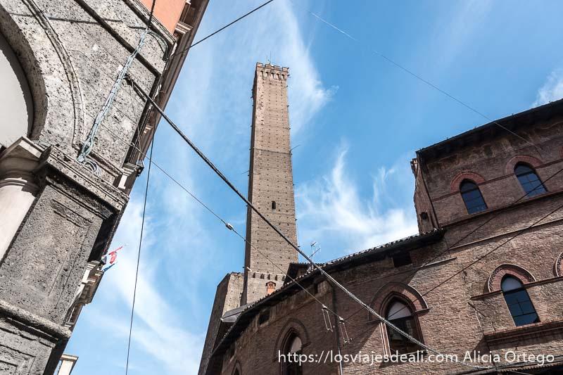 torre asinelli desde abajo entre cables de tranvía con cielo azul y nubes blancas