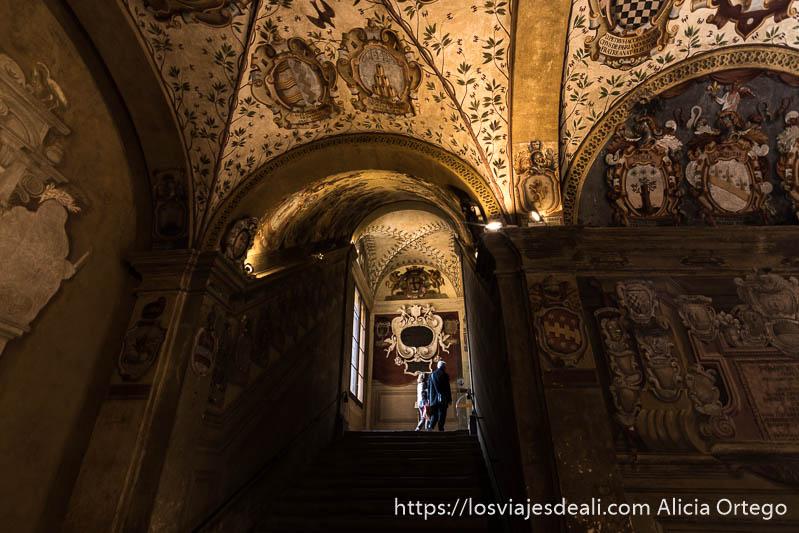 escaleras de subida en la biblioteca con techos llenos de pinturas con escudos de armas y motivos vegetales imprescindibles de bolonia