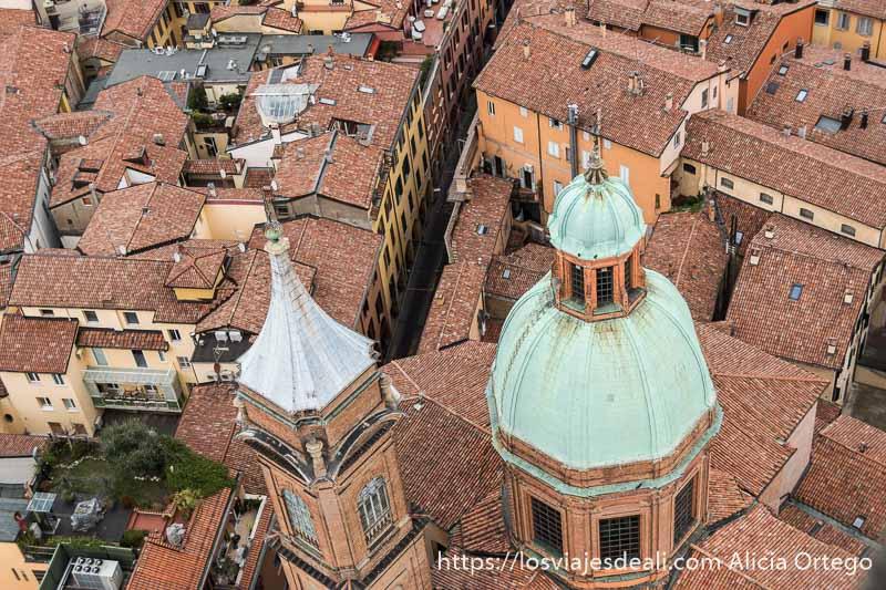 vista aérea de cúpula verde y torre junto a ella con tejados de tejas rojas imprescindibles de bolonia