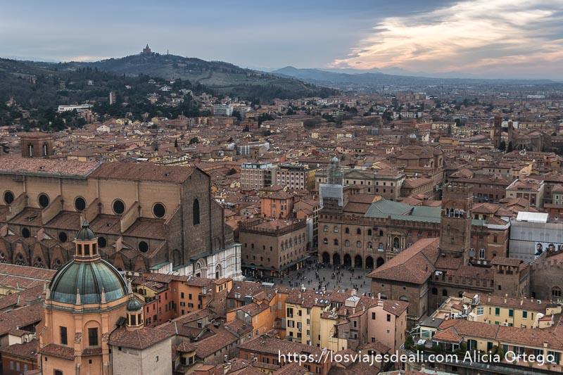 vista de la plaza magiore con monte al fondo y luz de atardecer desde la torre asinelli imprescindibles de bolonia