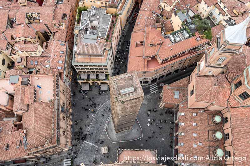 vista cenital de la torre garisenda con palacios alrededor con tejados de tejas y gente como si fuera hormigas imprescindibles de bolonia