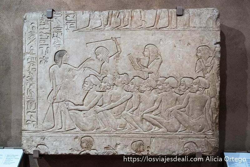 relieve egipcio donde se ve grupod e esclavos negros sentados y capataz levantando látigo en el museo arqueológico de bolonia