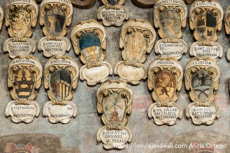 pared llena de escudos de universitarios imprescindibles de bolonia