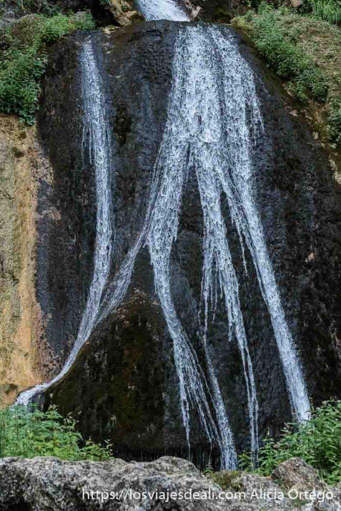 cascada del nacimiento del río mundo cayendo por gran roca y dividiéndose en la parte inferior por otra roca que sobresale