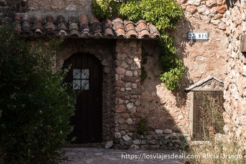 puerta de casa en muro de piedra con tejadillo de tejas y plantas enredaderas escapada a albacete