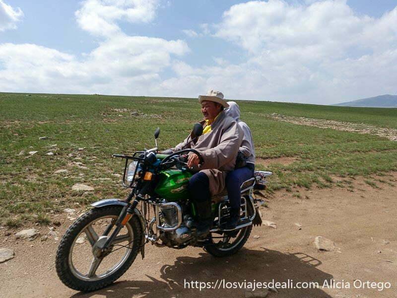 pareja de mongoles circulando en moto en una pradera del valle de orkhon