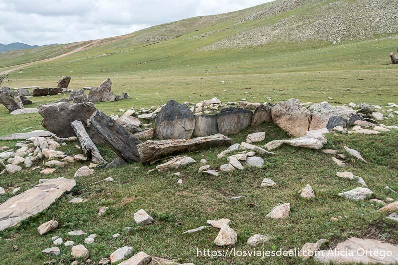 tumba de la edad de bronce de forma rectangular con piedras haciendo paredes en una pradera verde del valle de orkhon