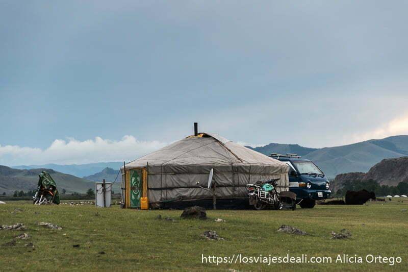 ger de nómadas con antena parabólica, dos motos junto a la tienda y una furgoneta azul