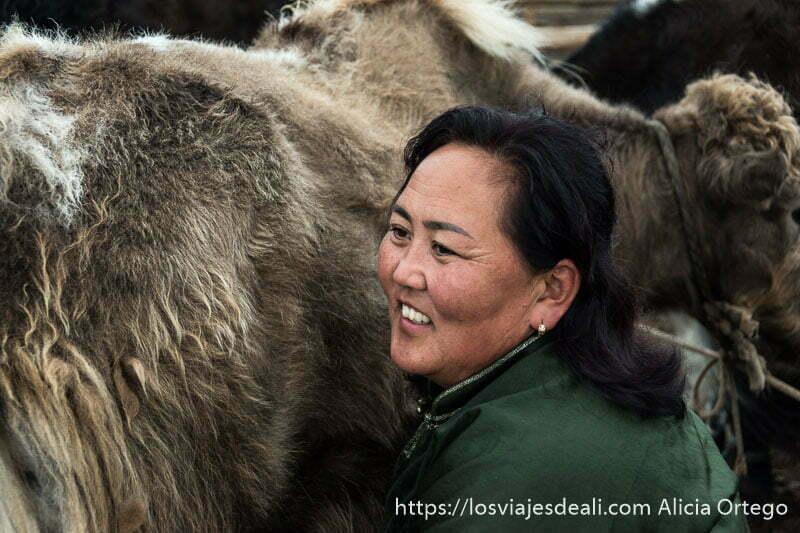 primer plano de la mujer mongol con su vestido verde ordeñando a un yak en el valle de orkhon