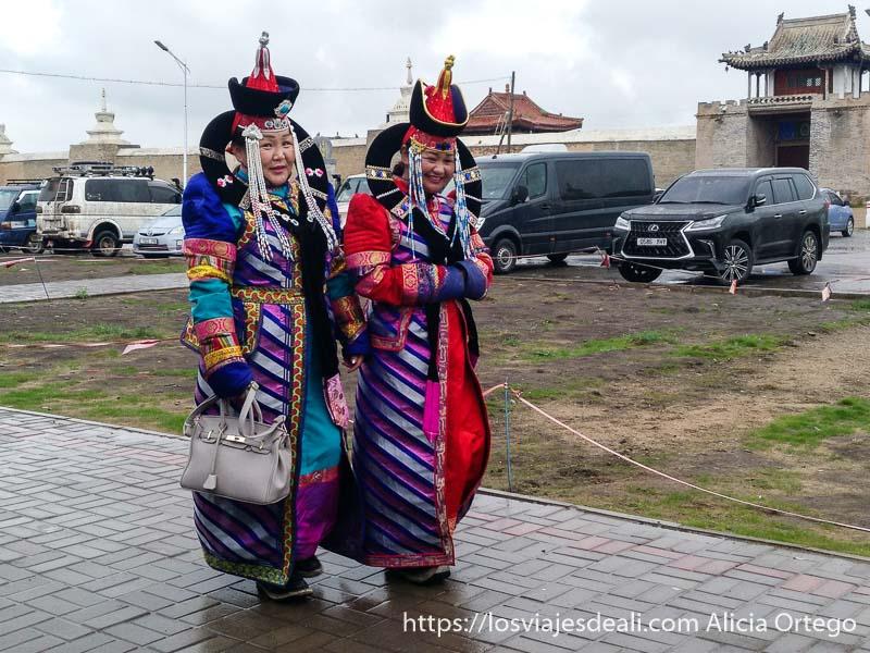 dos mujeres vestidas con trajes antiguos de la corte mongol andando sonrientes en karakorum