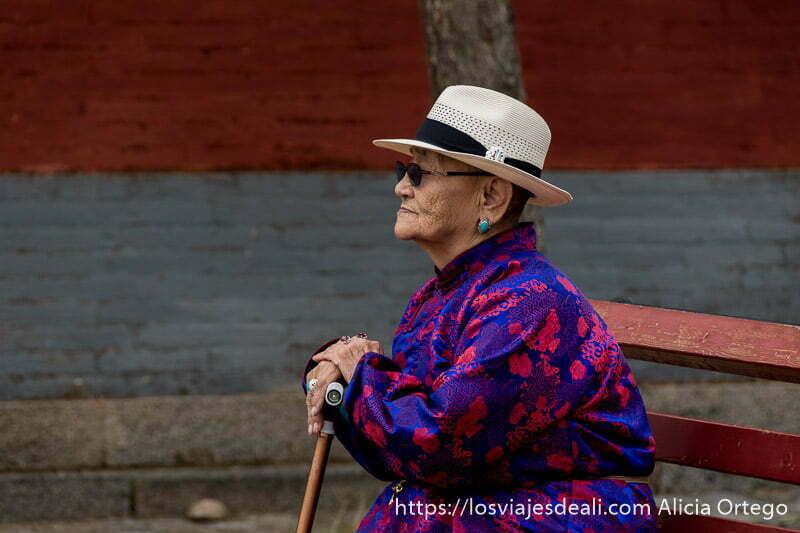 anciana mongol con vestido tradicional en color azul con dibujos rojos sentada en un banco apoyada en su bastón
