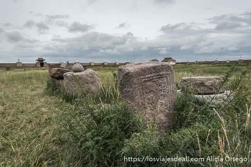 piedras con símbolos grabados semienterradas en la hierba dentro del monasterio de karakorum