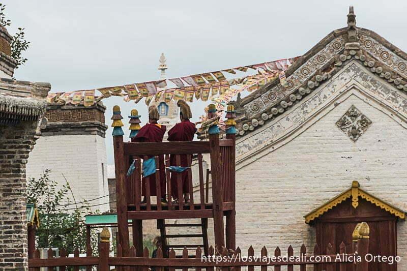 dos monjes budistas con gorro amarillo subidos a una pequeña torre de madera junto al templo con banderitas en karakorum