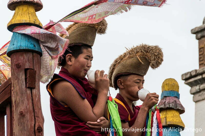 dos monjes niño budistas tocando caracolas de mar que tienen pañuelos de seda de colores en el extremo