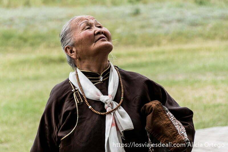 abuela mongol con rosario alrededor del cuello mirando hacia el cielo en karakorum