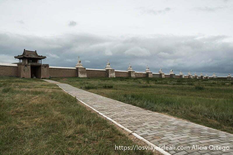 camino empedrado en el gran patio del monasterio de ederne zuu y muralla de ladrillo con estupas blancas bajo cielo nublado