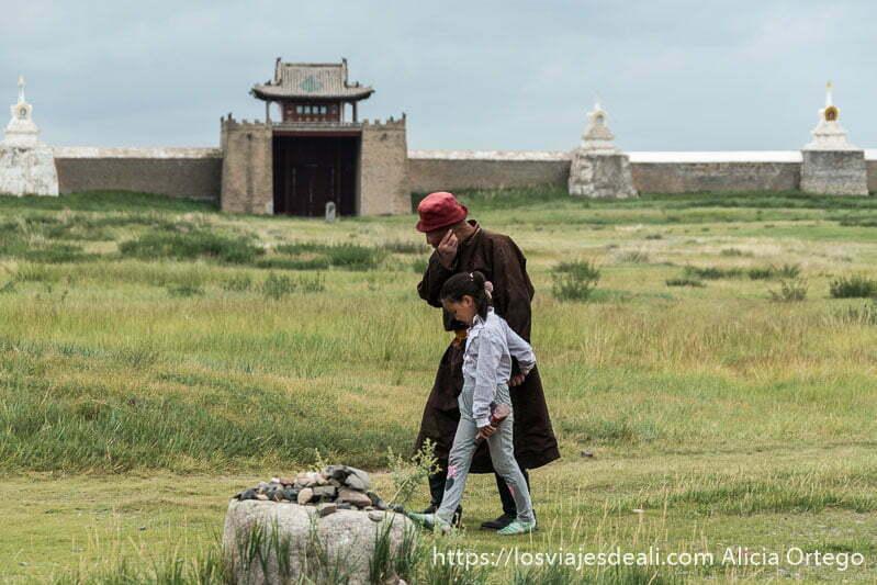 abuelo y nieta mongoles paseando con las murallas del monasterio detrás