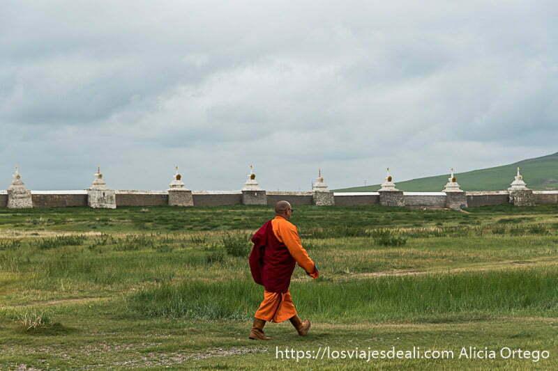 monje budista con hábito naranja y rojo y botas altas de piel andando con las murallas de karakorum al fondo