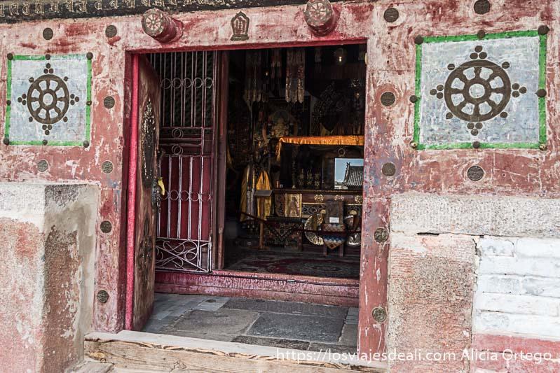 puerta de templo abierta desde donde se ve estatuas de buda en karakorum