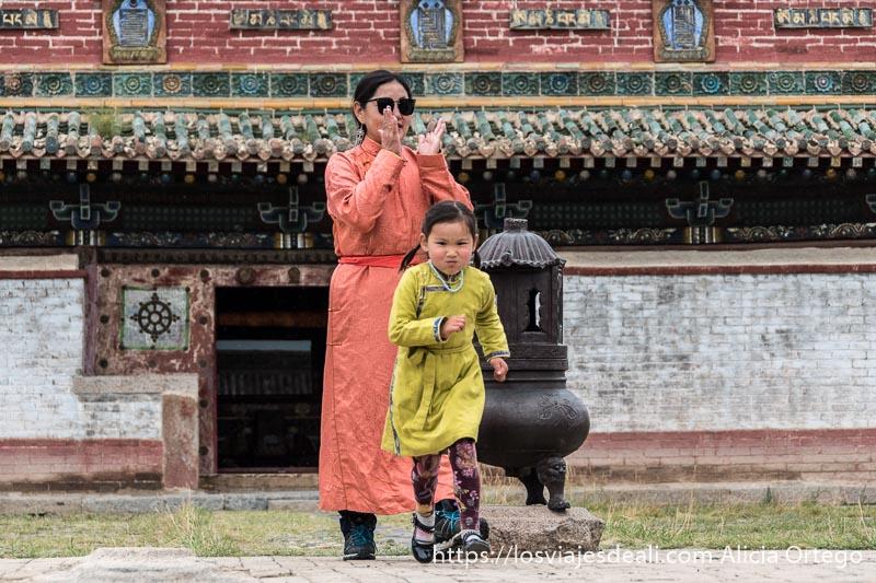 niña con vestido amarillo corriendo hacia la cámara y su madre con túnica de color salmón detrás aplaudiendo y al fondo un templo de colores verde y rojo en karakorum
