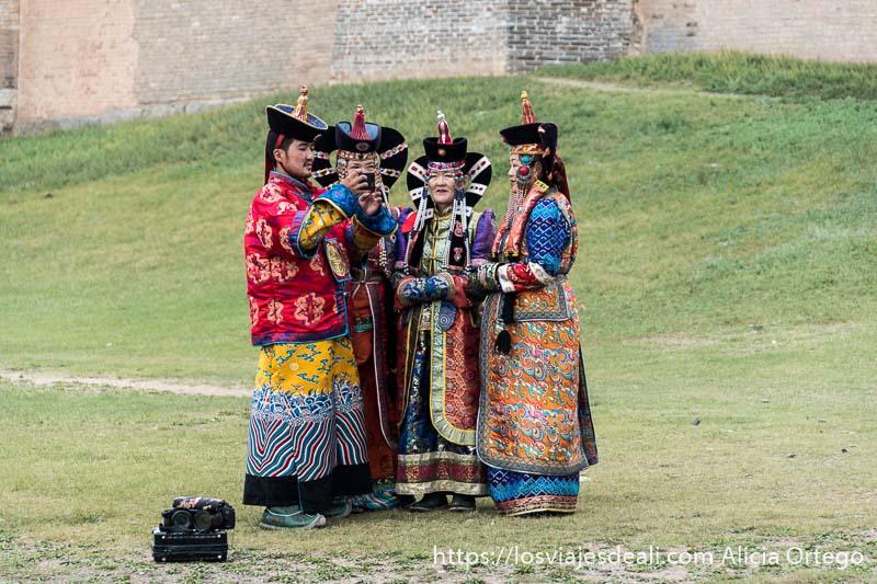 grupo de turistas mongoles vestidos con trajes antiguos de la corte y un tocado en el cabello de color negro que termina en gorro haciendo un selfie con el móvil