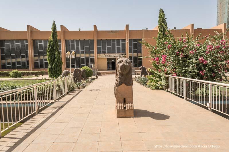 estatua antigua de león delante de la puerta del museo nacional de sudán