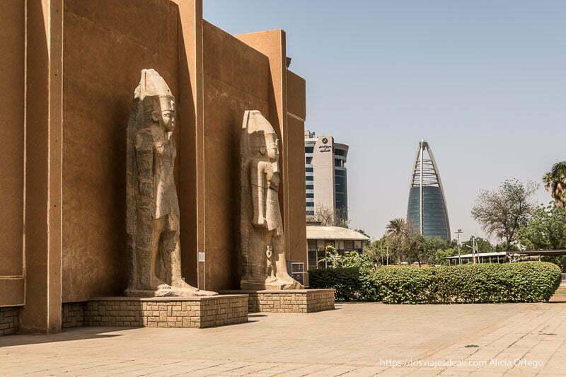 dos estatuas de faraones con pie adelantado en los muros del museo nacional y al fondo edificio futurista en forma de cono en jartum