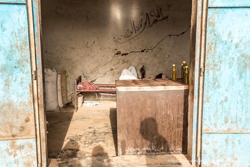 puerta con mostrador donde hay tres botellas de aceite y un señor al fondo tumbado en camastro mirando su móvil en sudán