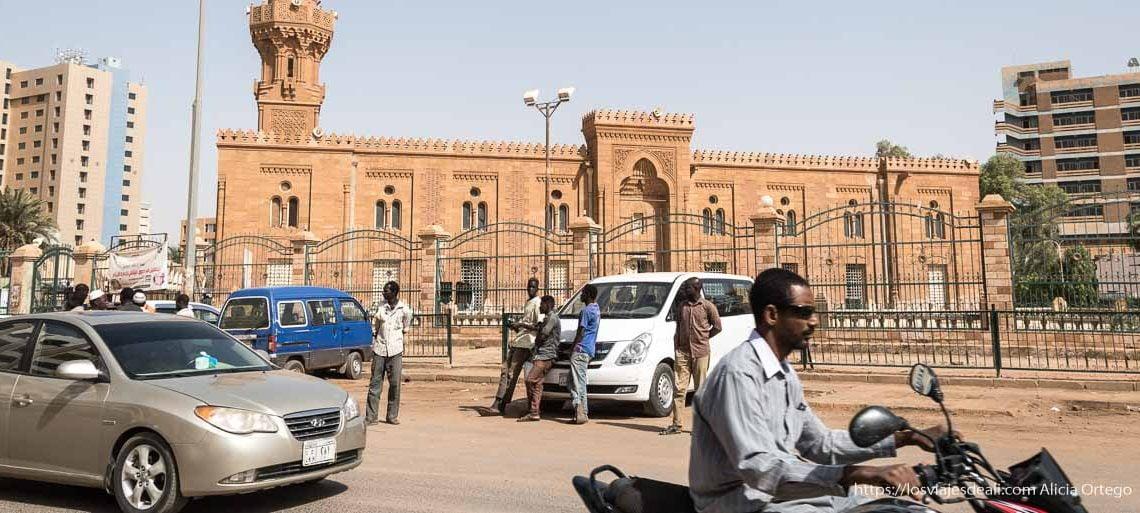 mezquita de arenisca en el centro de jartum y tráfico delante con señor en moto con gafas de sol sin casco y otros apoyados en minibus