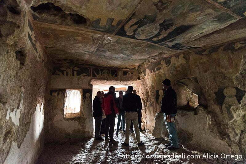 grupo de visitantes en el centro de la iglesia de ivanovo rodeados de pinturas en paredes y techo sitio patrimonio de la humanidad de bulgaria