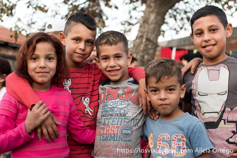 cinco niños gitanos de bulgaria sonrientes posando para la foto son cuatro chicos y una niña con gersey rosa