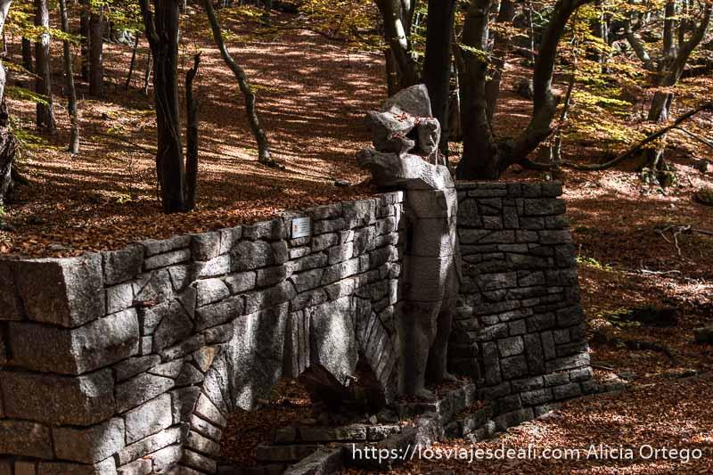 monumento de piedra a los soldados rusos es una figura mirando de lado con puño en levantado en la misma dirección en medio del bosque