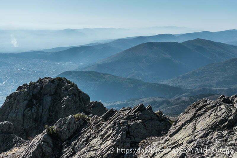 montes balcanes con colores azulados y rocas en primer plano abajo a la derecha se ve la ciudad de sliven