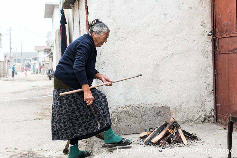 abuela arreglando la lumbre en la acera de la calle para preparar pan tradicional en la mahala de los gitanos de bulgaria