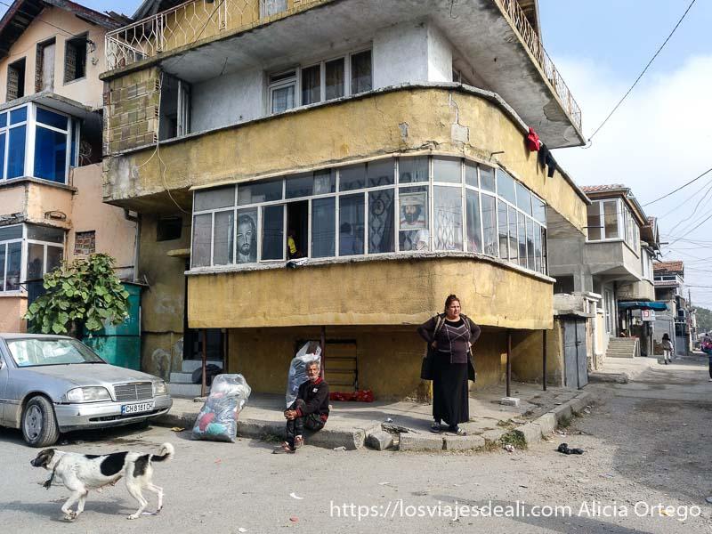 casa de la plaza haciendo esquina con balcón acristalado y un póster de jesucristo y una mujer de pie en la esquina y un hombre sentado en la acera