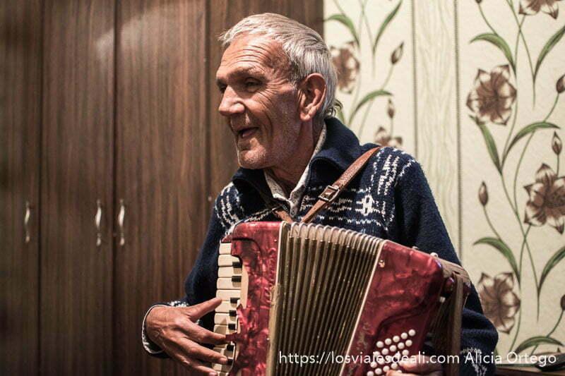 anciano gitano tocando el acordeón en su dormitorio detrás hay pared con papel de flores