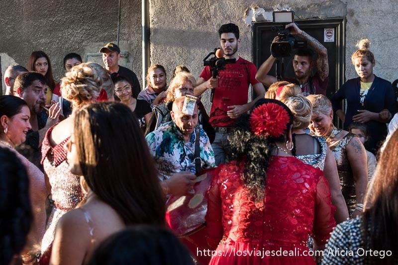 mujeres bailando alrededor de músico con billete en la frente y detrás los cámaras de la boda grabando gitanos de bulgaria