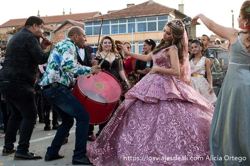 novia vestida de princesa baila echándose hacia atrás delante de los músicos y alrededor invitadas con vestidos de fiesta en la plaza de sliven