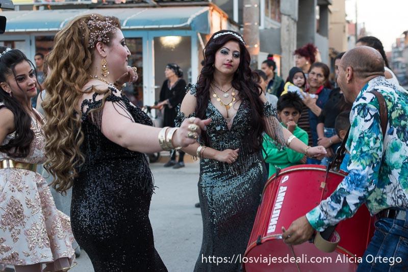dos invitadas de boda bailando frente al que toca el tambor. Llevan vestidos negros con lentejuelas y grandes escotes