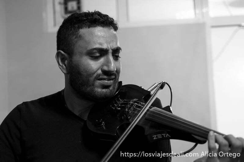 el violinista bocidar tocando con su violín con cara concentrada en el barrio de los gitanos de bulgaria