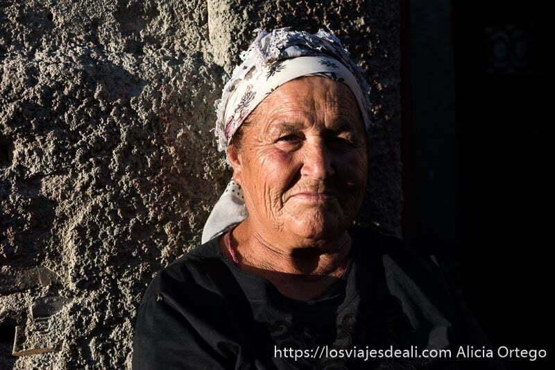 abuela de la mahala de sliven con pañuelo anudado en la cabeza y sol de atardecer gitanos de bulgaria