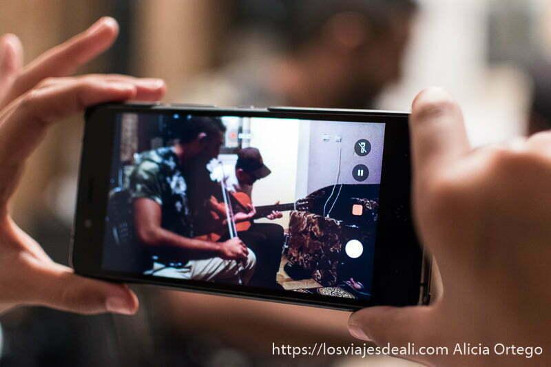 pantalla de móvil grabando a violinista y guitarrista en la casa de sliven gitanos de bulgaria