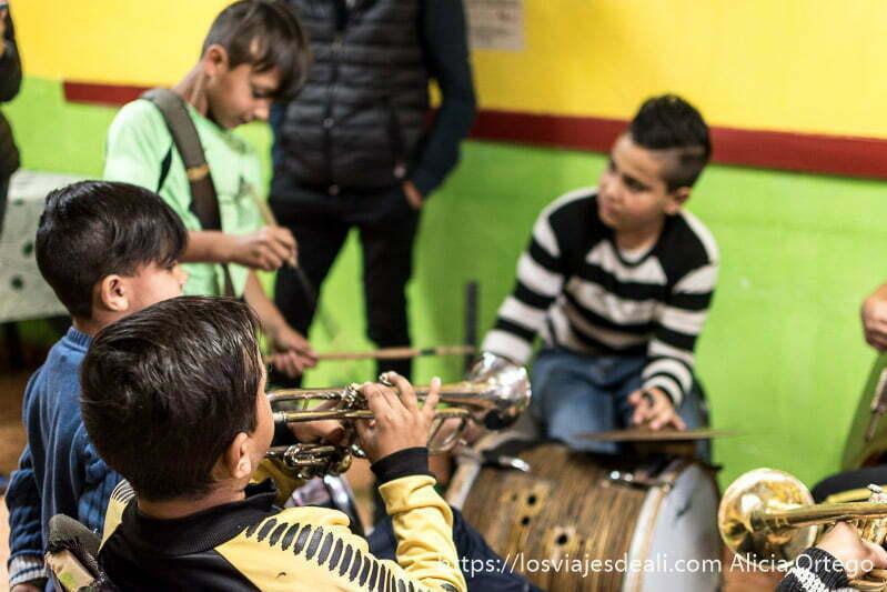 niños tocando trompeta y tambores en la escuela de la mahala de sliven con paredes pintadas de colores verde, rojo y amarillo gitanos de bulgaria