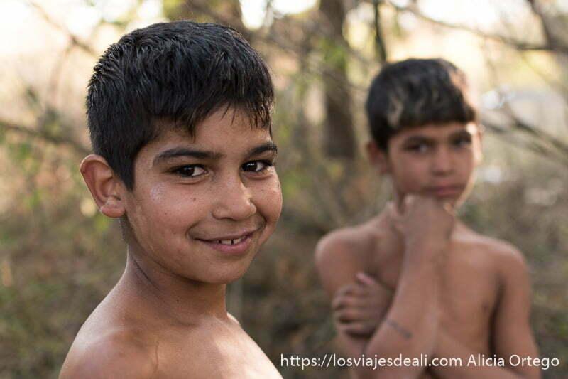 retrato de dos niños laho uno en primer plano sonriendo a la cámara con ojos muy negros y el otro al fondo desenfocado