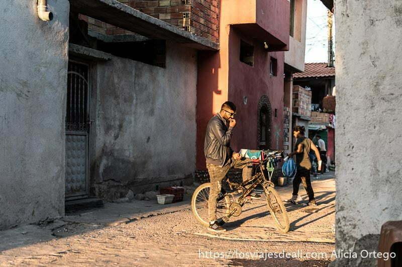 calle de la mahala con chico montado en bici y gafas de sol y sol de atardecer gitanos de bulgaria
