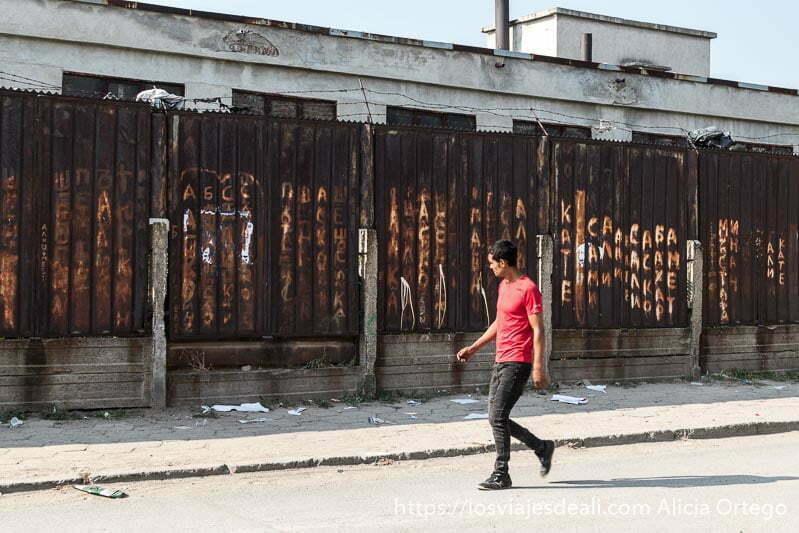 muro de la mahala de sliven de chapa oxidada lleno de pintadas y un chico pasando delante con camiseta roja y pantalones negros