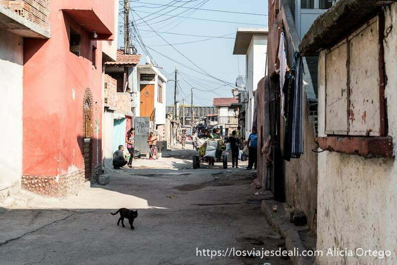 calle de la mahala de sliven con un gato negro cruzando y al fondo gente y un carro
